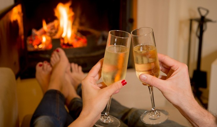 Couple drinking champagne by the fire. Photo: Ocus Pocus / Bigstock.com