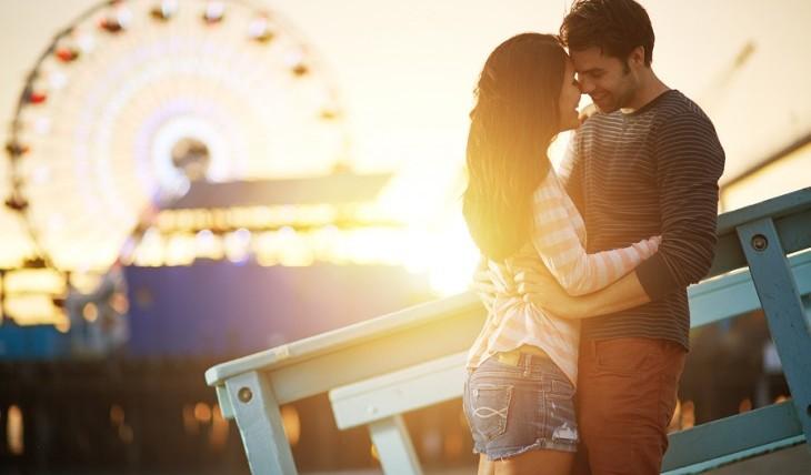 Romantic couple kissing in front of a ferris wheel at an amusement park. Photo: evren_photos / Bigstock.com